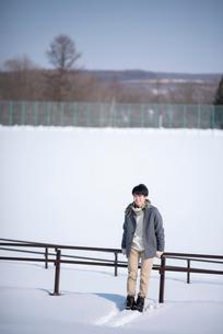 柵に寄りかかり微笑む男性の写真素材 [FYI03421983]