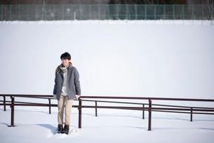 柵に寄りかかり微笑む男性の写真素材 [FYI03421984]
