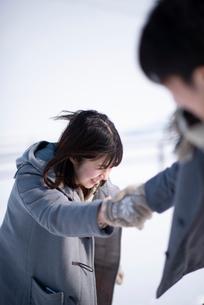 雪原で手をつなぐカップルの写真素材 [FYI03421988]