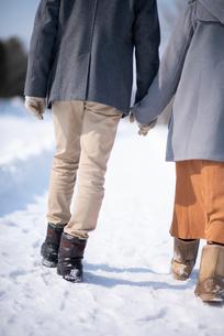 雪道を歩くカップルの足元の写真素材 [FYI03421991]