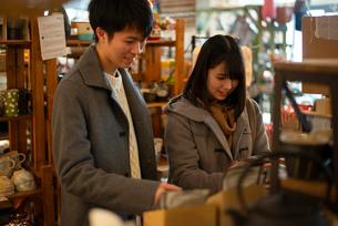 雑貨屋で買い物をするカップルの写真素材 [FYI03422003]