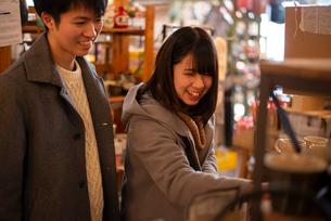 雑貨屋で買い物をするカップルの写真素材 [FYI03422004]