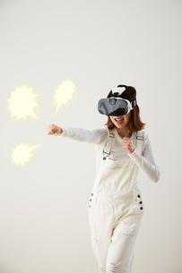 白壁の前でVRをつけてパンチをする女性の写真素材 [FYI03422611]
