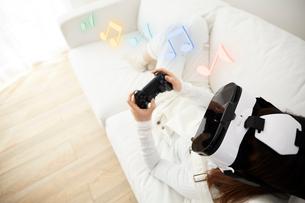 ソファに寝転がってVRをつけてゲームをする女性の写真素材 [FYI03422612]