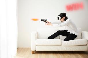 ソファの上でVRをつけてシューティングゲームをする男性の写真素材 [FYI03422614]