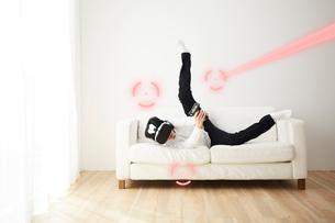 ソファの上でVRをつけてシューティングゲームをする男性の写真素材 [FYI03422615]
