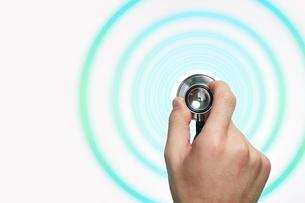 聴診器を持つ手とその周りに広がる円の写真素材 [FYI03422617]