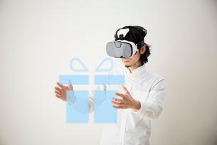 CGのプレゼントボックスを持つVRを着けた男性の写真素材 [FYI03422633]