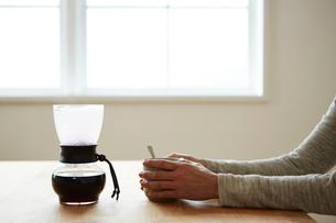 サイフォンに入ったコーヒーとカップを持つ女性のの手元の写真素材 [FYI03422761]