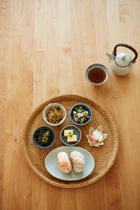 テーブルの上の丸いトレーにセットされたおにぎりと小鉢の写真素材 [FYI03422795]