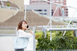 建物の2階の柵に腕をのせながら電話をする女性の写真素材 [FYI03422850]