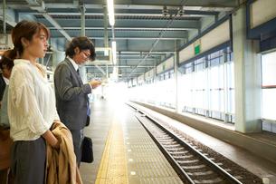 駅のホームで電車を待つ男女の写真素材 [FYI03422883]
