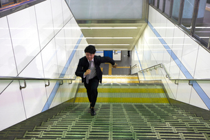 ホームの階段を駆け上がるビジネスマンの写真素材 [FYI03422887]