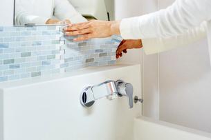 洗面所の壁にタイルシートを貼る女性の手の写真素材 [FYI03422895]