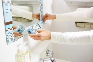 鏡にマスキングテープを貼る女性の手の写真素材 [FYI03422909]