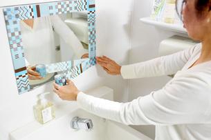 鏡にマスキングテープを貼る女性の手の写真素材 [FYI03422910]