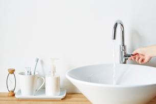 ナチュラルな洗面台で水を出す女性の手の写真素材 [FYI03422918]