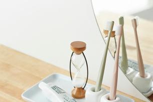 鏡の前の2本の歯ブラシと砂時計の写真素材 [FYI03422923]