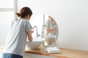 木天板の洗面で洗顔をする女性の写真素材 [FYI03422925]