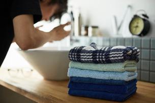 ナチュラルな洗面台に積まれた寒色のタオルと顔を洗う男性の写真素材 [FYI03422933]
