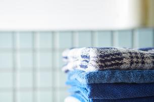 積まれた青いタオルと水色のタイル壁の写真素材 [FYI03422937]