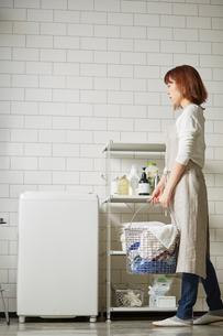 白いタイル壁のランドリースペースで洗濯をする女性の写真素材 [FYI03422941]