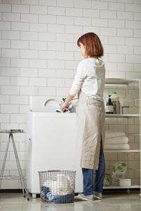 白いタイル壁のランドリースペースで洗濯をする女性の写真素材 [FYI03422942]