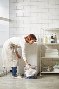 白いタイル壁のランドリースペースで洗濯をする女性の写真素材 [FYI03422943]