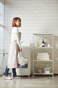 白いタイル壁のランドリースペースで洗濯をする女性の写真素材 [FYI03422944]