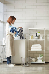 白いタイル壁のランドリースペースで洗濯をする女性の写真素材 [FYI03422947]