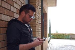 携帯を操作する外国人の写真素材 [FYI03423121]