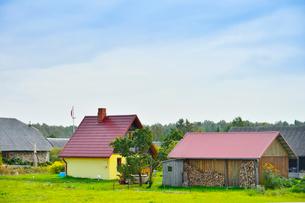 エストニア~ラトビア間車窓から見たカラフルな小さな家に薪が積まれた景観の写真素材 [FYI03423171]