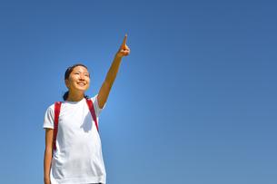 青空で指さす小学生の女の子(ランドセル)の写真素材 [FYI03423657]