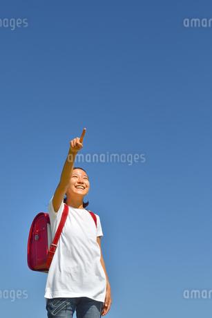 青空で指さす小学生の女の子(ランドセル)の写真素材 [FYI03423658]