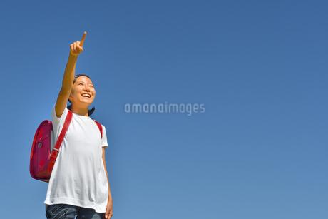 青空で指さす小学生の女の子(ランドセル)の写真素材 [FYI03423659]