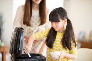 茶碗にご飯をよそう女の子の写真素材 [FYI03423830]