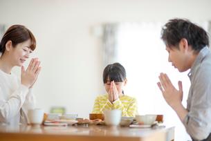 食事を前に手を合わせる家族の写真素材 [FYI03423837]