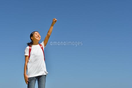 青空でガッツポーズをきめる小学生の女の子(ランドセル)の写真素材 [FYI03424171]