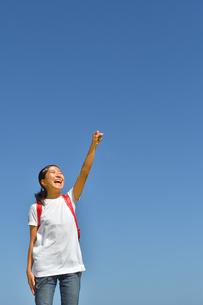青空でガッツポーズをきめる小学生の女の子(ランドセル)の写真素材 [FYI03424173]