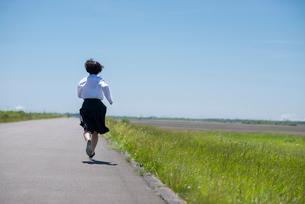 土手を走る女子学生の後ろ姿の写真素材 [FYI03424385]