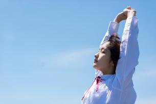 青空の中で伸びをする女子学生の写真素材 [FYI03424396]