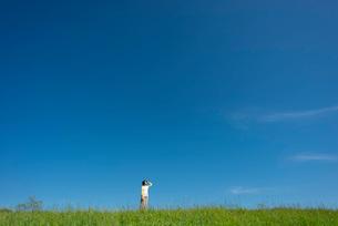 草原の中で空を見上げる若い女性の写真素材 [FYI03424417]