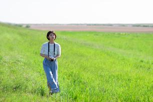 カメラを持ち土手を歩く若い女性の写真素材 [FYI03424433]