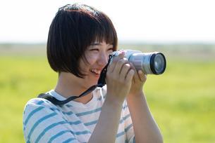 草原でカメラを持つ若い女性の写真素材 [FYI03424434]