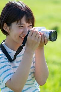 草原でカメラを持つ若い女性の写真素材 [FYI03424435]