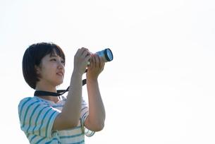 空の下でカメラを構える若い女性の写真素材 [FYI03424436]