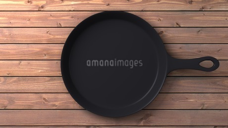 Cast iron skillet on wood backgroundのイラスト素材 [FYI03424666]