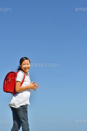 青空で笑う小学生の女の子(ランドセル)の写真素材 [FYI03424690]
