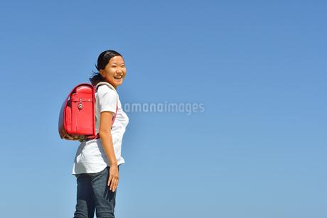 青空で笑う小学生の女の子(ランドセル)の写真素材 [FYI03424691]