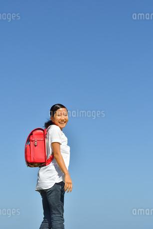 青空で笑う小学生の女の子(ランドセル)の写真素材 [FYI03424692]